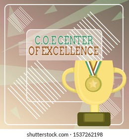 Word writing text Coe Center Of Excellence. Business concept for being alpha leader in your position Achieve Trophy Cup on Pedestal with Plaque Decorated by Medal with Striped Ribbon.