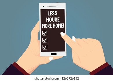 Word writing text Less House More Home. Business concept for Have a warm comfortable place to live with family love Hu analysis Hands Holding Pointing Touching Smartphone Blank Color Screen.