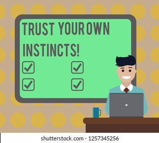 Word writing text Trust Your Own Instincts. Business concept for Intuitive follow demonstratingal feelings confidence Blank Bordered Board behind Man Sitting Smiling with Laptop Mug on Desk.