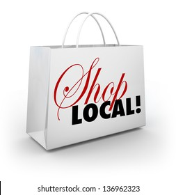 The words Shop Local on a white shopping bag encouraging you to support your local community or hometown by buying merchandise in your backyard and keeping money nearby