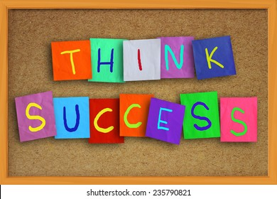 The words Think Success written on sticky colored paper over cork board
