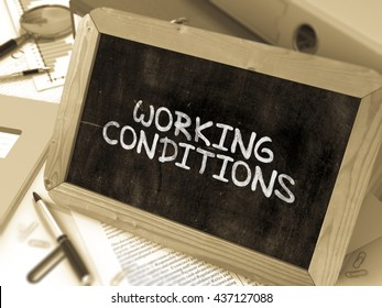 Working Conditions Concept Hand Drawn on Chalkboard on Working Table Background. Blurred Background. Toned Image. 3D Render.