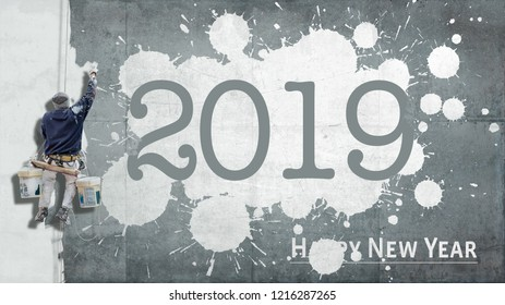 Workman hanging from a building writing the words Happy New Year 2019