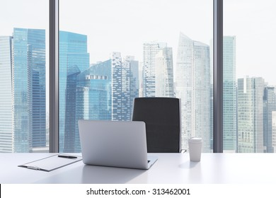 A workplace in a modern panoramic office with Singapore view. A white table, black leather chair. Laptop, writing pad for notes and a cap of coffee are on the table. Office interior. 3D rendering.