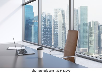 A workplace in a modern panoramic office with Singapore view. A grey table, brown leather chair. Laptop, writing pad for notes and a cap of coffee are on the table. Office interior. 3D rendering.