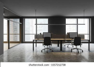 Workplace in stylish open space office with gray walls, concrete floor, big windows with cityscape and gray computer tables with black chairs. 3d rendering