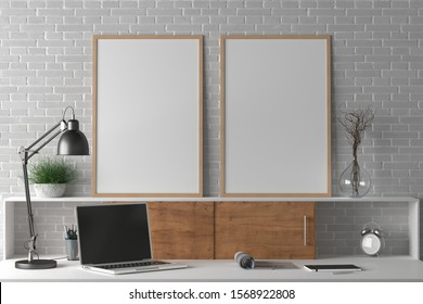 Workspace with two vertical poster mock ups on the desk. Desk with drawers in interior of the studio or at home with white brick wall. Clipping path around poster. 3d illustration.