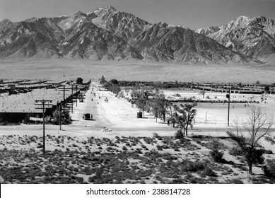 World War II, Bird's-eye view of Manzanar Relocation Center, showing buildings, roads, and Sierra Nevada mountains in background. California. photograph by Ansel Adams. 1943