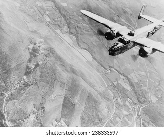 World War II, a Nazi supply dump goes up in smoke. A U.S. B-25 medium bomber roars over Tivoli, Nazi supply center ten miles east of Rome. Italy, photograph, 1940-1946.