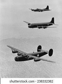 World War II, United States planes in echelon formation, from the top: Boeing Flying Fortress B17, Douglas Transport, Consolidated Liberator B-24, ca 1942.