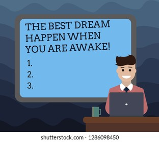 Writing note showing The Best Dream Happen When You Are Awake. Business photo showcasing Stop dreaming start acting Bordered Board behind Man Sitting Smiling with Laptop Mug on Desk.