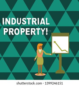 Writing note showing Industrial Property. Business photo showcasing the intangible ownership of a trademark or patent Woman Holding Stick Pointing to Chart of Arrow on Whiteboard.