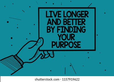 Writing note showing Live Longer And Better By Finding Your Purpose. Business photo showcasing Look for a goal set mission Man hand holding paper communicating dotted turquoise background.
