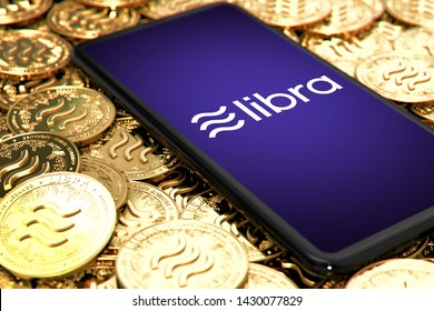 WROCLAW, POLAND - JUNE 20th, 2019: Facebook announces Libra cryptocurrency. Smartphone with Libra logo on the screen is laying down on Libra concept coins - 3D rendering