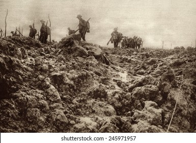 WWI. Western front battleground has been churned up by shell explosions so that it bears no resemblance to its peacetime appearance. Allied soldiers are in the background. Ca. 1915-18.