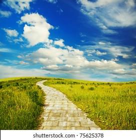 yellow brick road through green meadows, fantasy background