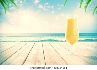 Yellow cocktail glass on wooden surface at the beach with palm trees. 3D Rendering