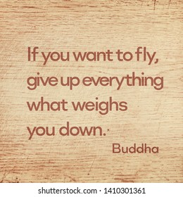 If you want to fly, give up everything what weighs you down - famous quote of Gautama Buddha printed on grunge wooden board