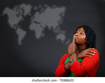 young African American woman thinking and looking at the world map with a positive attitude.