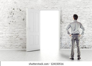 young business man in front of an open door in a vintage white brick wall