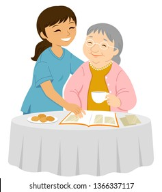 Young female caregiver smiling to an elderly woman who is placing photos in an album