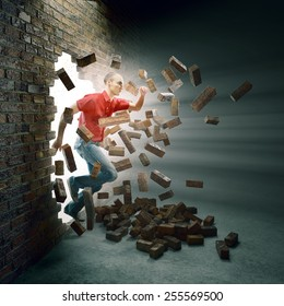 Young man running through a brick wall