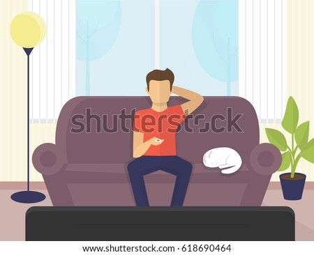 29e9a2f3be8e Young man sitting at home on the sofa watching tv and relaxing with cat.  Flat