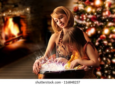 Young mother and her little daughter reading book sitting at the Christmas tree, fireplace