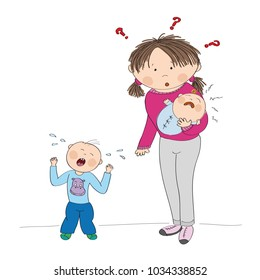 Young mother holding little crying baby boy, her second child, little toddler is standing, screaming, having temper tantrum