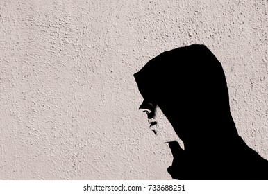 Young teenage bully boy in black hoodie with graffiti stencil effect on white wall with copy space