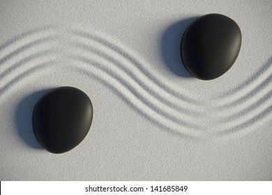Zen garden on sand with two black stones separated by a drawing ripples