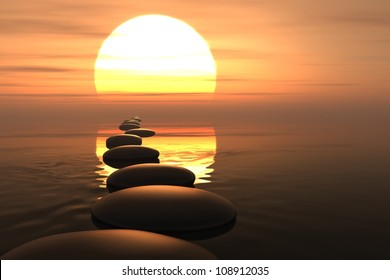 Zen stones into the water with sunset on the background