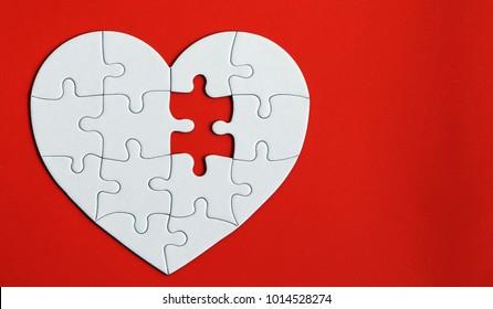 Heartpuzzleontheredbackground. Amissingpieceoftheheartpuzzle.