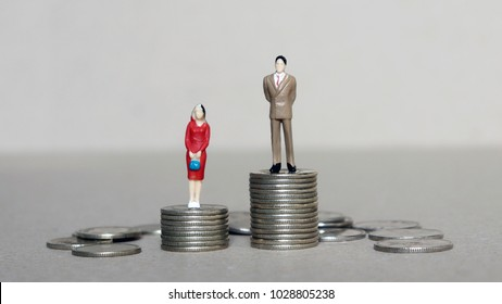 Gender pay gap concept. A miniature man and a miniature woman standing in a pile of coins.