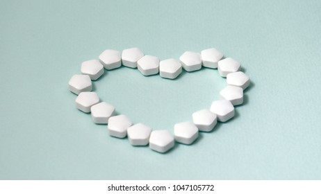 Heart shaped white pills on soft jade green background.