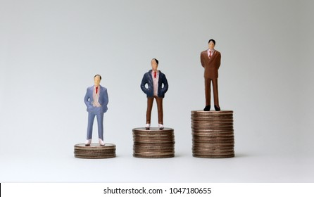 Miniature men standing on top of three coins of different heights.