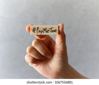 #PayMeTooasanewmovementconcept.  Handholdingawoodenblockwith#PayMeToo
