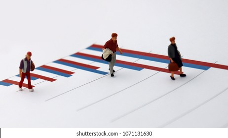 Miniature people standing on top of a bar graph. A concept of economic inequality.