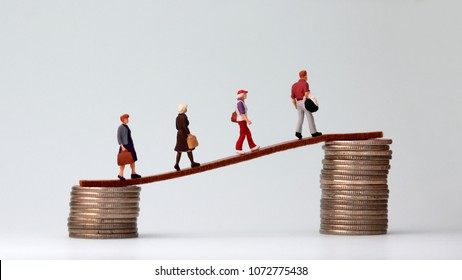 Miniature people walking from low to high pile of coins. The concept of the gap between the rich and the poor.