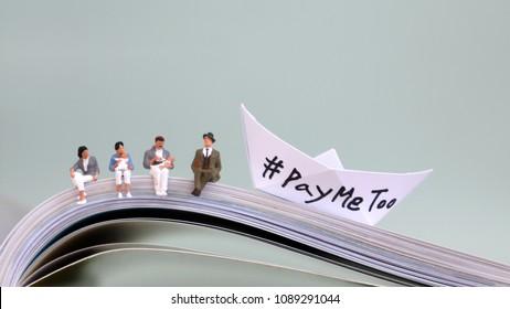 #PayMeTooassocialnewmovement.Sittingminiaturepeopleandwhite paperboatwith'#PayMeToo'onan openbook.