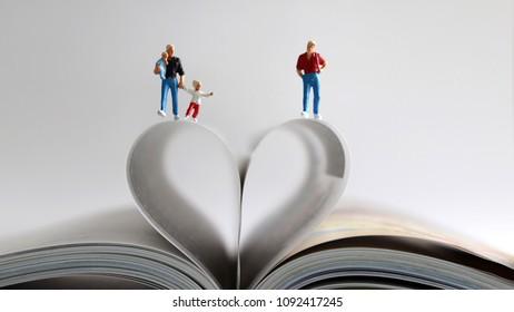 Same-sexcoupleandfamilyloveconcept. Gaycouplewalkingwithbabyonthebookwithopenedpagesandshapeofheart.