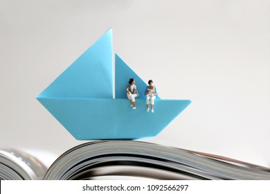 A miniature lesbian couple sitting with their baby in a blue paper boat on an open book page. Same-sex couple and family love concept.