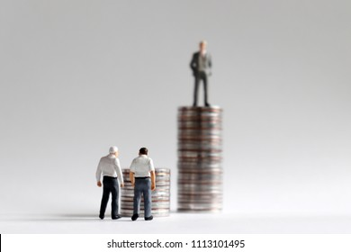 The concept of social issues in economic difficulties due to rapid retirement in an aging society. The stack of coins with miniature people.