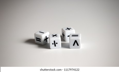 Four white dice with mathematical math symbols.