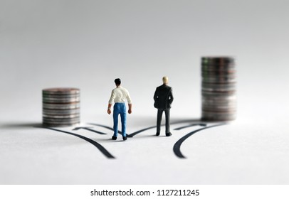 Two miniature men standing in front of two paths with a stack of coins of different heights.