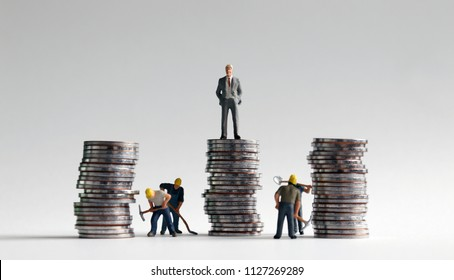 Miniature people and three pile of coins.