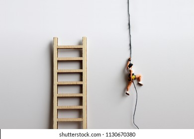 A miniature woman climbs a rope beside a wooden ladder.