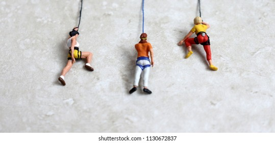 Competing social concepts. Miniature of three climbers.