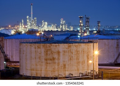 Natural gas storage tank and oil refinery at night