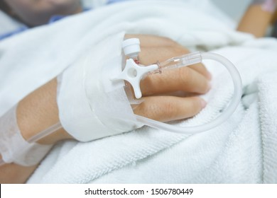 focus​on​ the​ hand​ of​ a​ patient​ in​ hospital​ ward.​ closeup​ of​ a​ woman​ patient​ in​ hospital​ with​ saline​ intravenous​(iv)​